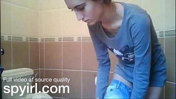 Худенькая девушка выделаывается перед камерой в туалете